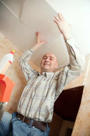 soffit cladding: Smiling man glues ceiling tile at home