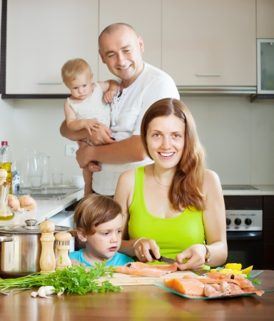 20 23 years: Happy family of four cooking salmon fish at home