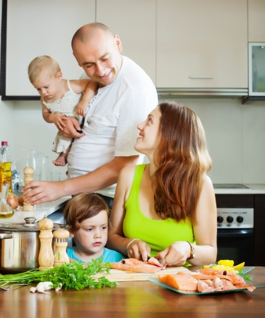 Happy family of four together in the kitchen prepares seafood Stock Photo - 21621914