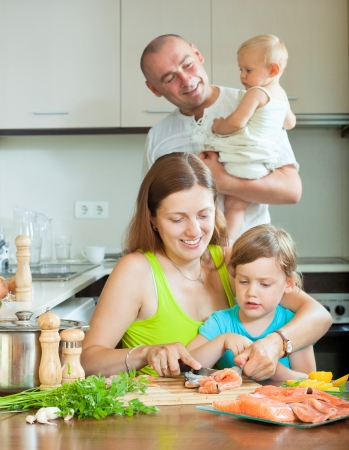 Happy parents with good kids cooking fish at home kitchen  Stock Photo - 21621916