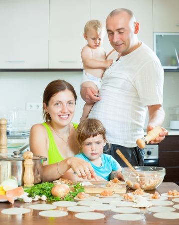 Happy family of four making small dumplings with fish (dumplings) in a home kitchen  photo