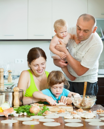 Happy parents with children dumplings fish cooking in a home kitchen  photo