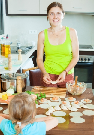 Happy woman with a child making fish dumplings freshest salmon stuffing and dough