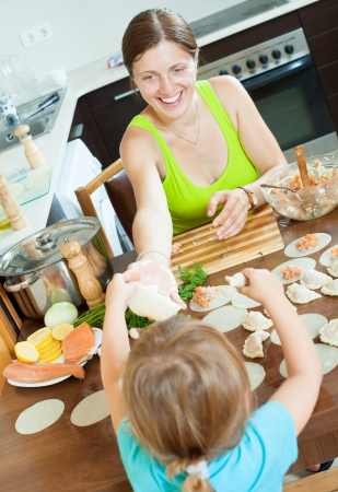 Happy woman with child cooking fish pelmeni (pelmeni), standing together  photo