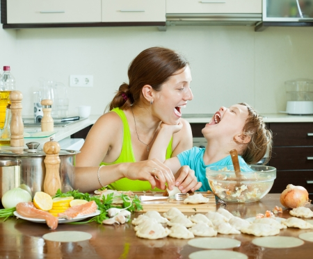 Smiling woman with child making fish dumplings from salmon  at domestic kitchen photo