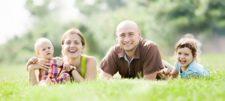 family of four enjoying time at green grass in summer p  photo