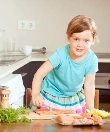 baby girl with raw salmon fish at home kitchen  photo