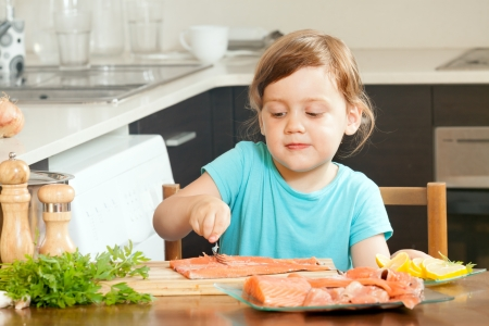 freshwater fish: Baby housewife cooking salmon at home kitchen  Stock Photo