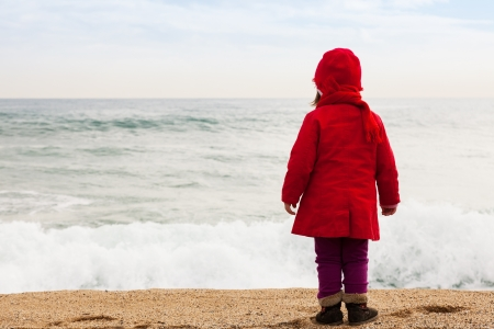aloneness: Baby girl on sand beach in cold windy day
