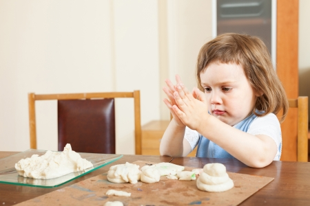 The child makes dough figurines in the room photo