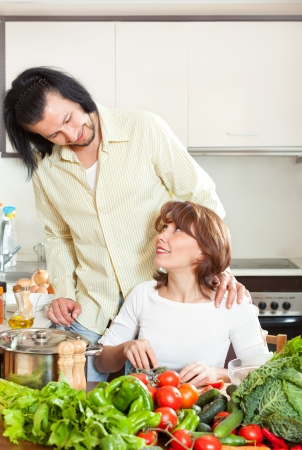 Brunette beautiful housewife with man cooking with fresh vegetables at home kitchen photo