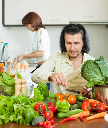 The couple preparing vegetable salad in my house photo