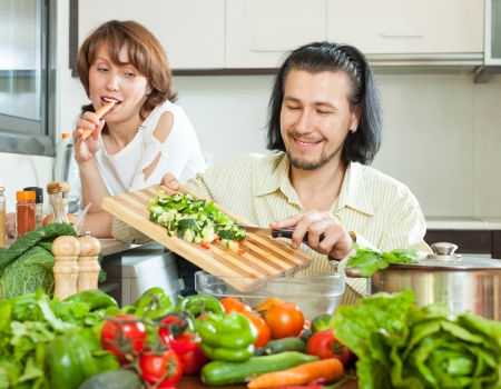 Cute couple preparing a meal of vegetables in your home photo