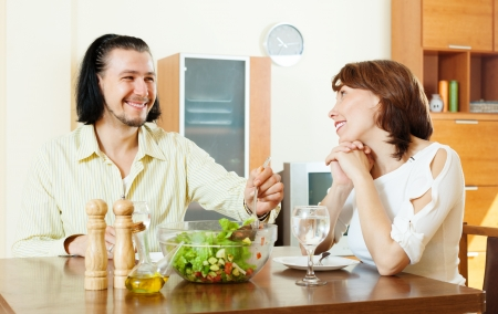 happy couple having lunch with vegetables in home  photo