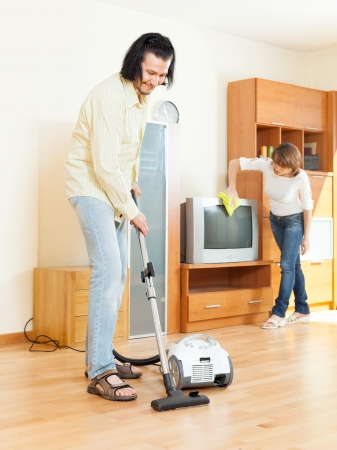 Happy middle-aged couple doing housework together in home photo