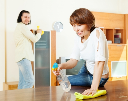 woman with husband cleaning living room at home photo