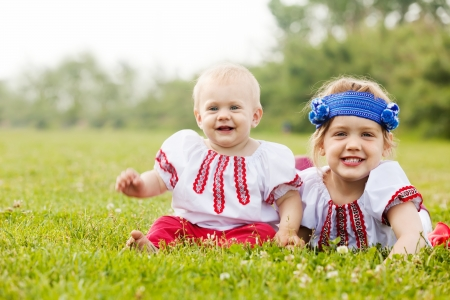 Two happy children in russian folk clothes on grass photo