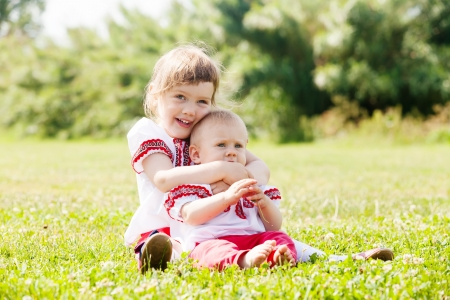 Two happy children in russian folk clothes on summer meadow photo