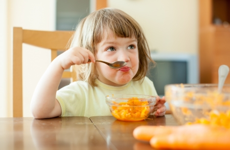 Little child eating carrot salad  in home photo