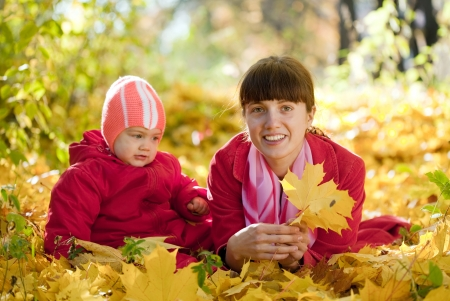 Mother and   baby laying on maple leaves in autumn park photo