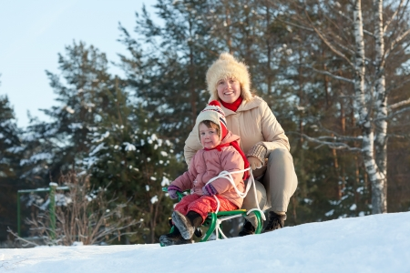 happy mother with 2 years child playing on slide in winter photo