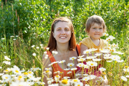 Happy mother with her daughter in summer camomile plant photo