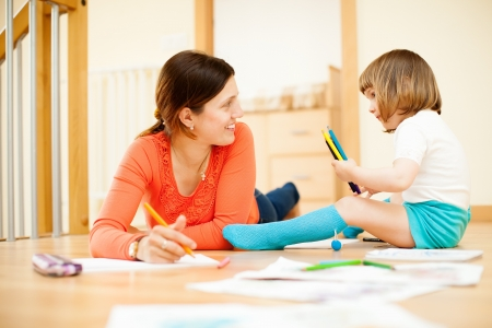 Happy mother and child drawing at parquet floor photo