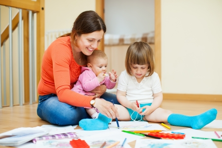 play of color: Happy mother with two children plays at home interior