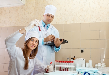 Doctor supervises the young nurse in a medical lab photo