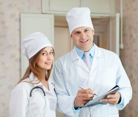 Portrait of doctor and nurse in hospital interior. Focus on man photo