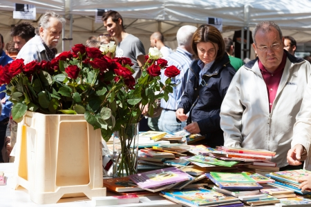 BARCELONA, SPAIN - APRIL 23: Sant Jordi feast - Catalan Saint George day in April 23, 2013 in Barcelona, Spain. Books and red roses is traditionally gifts of festival
