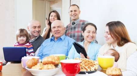 Happy family  uses electronic devices over tea in home interior at home photo