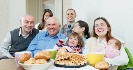 Portrait of happy multigeneration family or group of friends posing together over tea at home interior photo