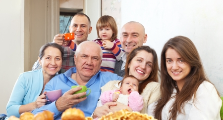Portrait of big happy family communicate over tea at home photo