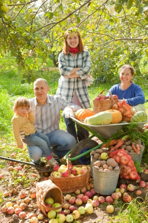 Happy  family with vegetables harvest in garden photo