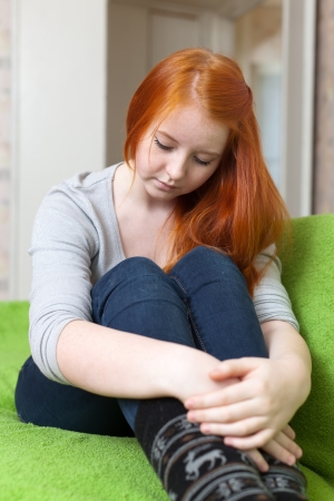 aloneness: Crying red-headed lonely teenager girl on sofa at  home
