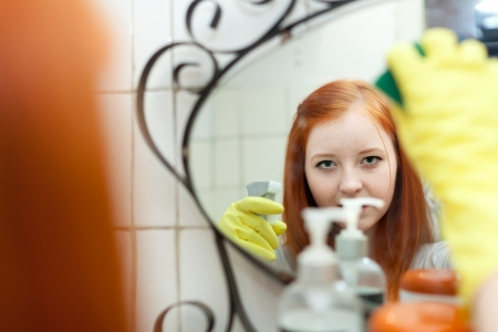 Teen girl  cleans mirror with sponge in bathroom at home  photo