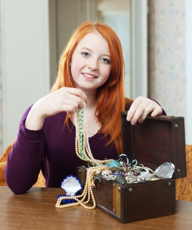 portrait of  red-headed teen girl looks jewelry in treasure chest