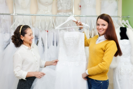 Mature woman  with daughter chooses white gown at shop of wedding fashion photo