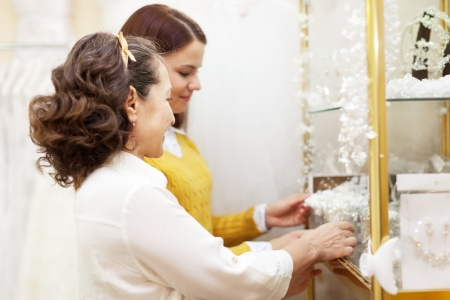 Two women  chooses bridal accessories in  boutique photo
