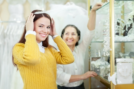 Mature saleswoman helps bride chooses bridal wreath at shop of wedding fashion photo
