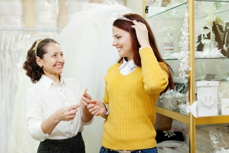 saleswoman helps bride chooses bridal accessories at shop of wedding fashion photo