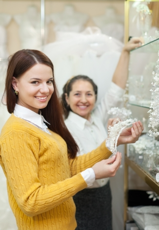 Two women  chooses bridal accessories in wedding boutique photo