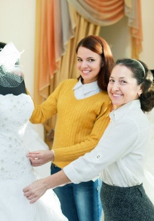 bridal salon: Mature saleswoman helps girl chooses white bridal gown at shop of wedding fashion. Focus on mature