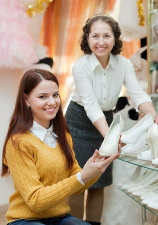 Shop assistant helps to girl chooses white shoes at shop of wedding fashion photo