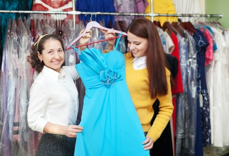 Two women chooses evening gown at fashion store photo