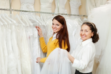 happy women chooses bridal clothes at wedding store. Focus on young bride  photo