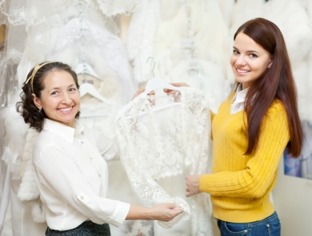 Mature woman helps the bride in choosing bridal clothes at shop of wedding fashion photo
