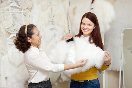 Two happy women chooses bridal outfit at wedding store. Focus on young woman photo