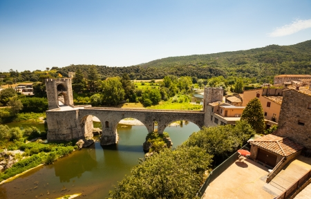 Wide angle shot of medieval bridge with gate tower. Besalu, Catalonia photo
